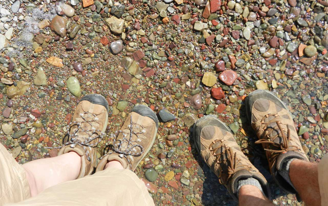 Woman's feet on the left, mans feet on the right - both wearing brown hiking boots - standing in shallow water surrounded by multicolored rocks.
