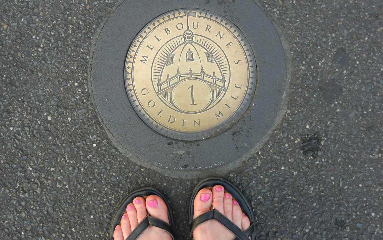 """Photo of feet with pink toenail polish and black sandals standing on blacktop next to a gold colored medallion with the words """"Melbourne's Golden Mile"""" on it."""