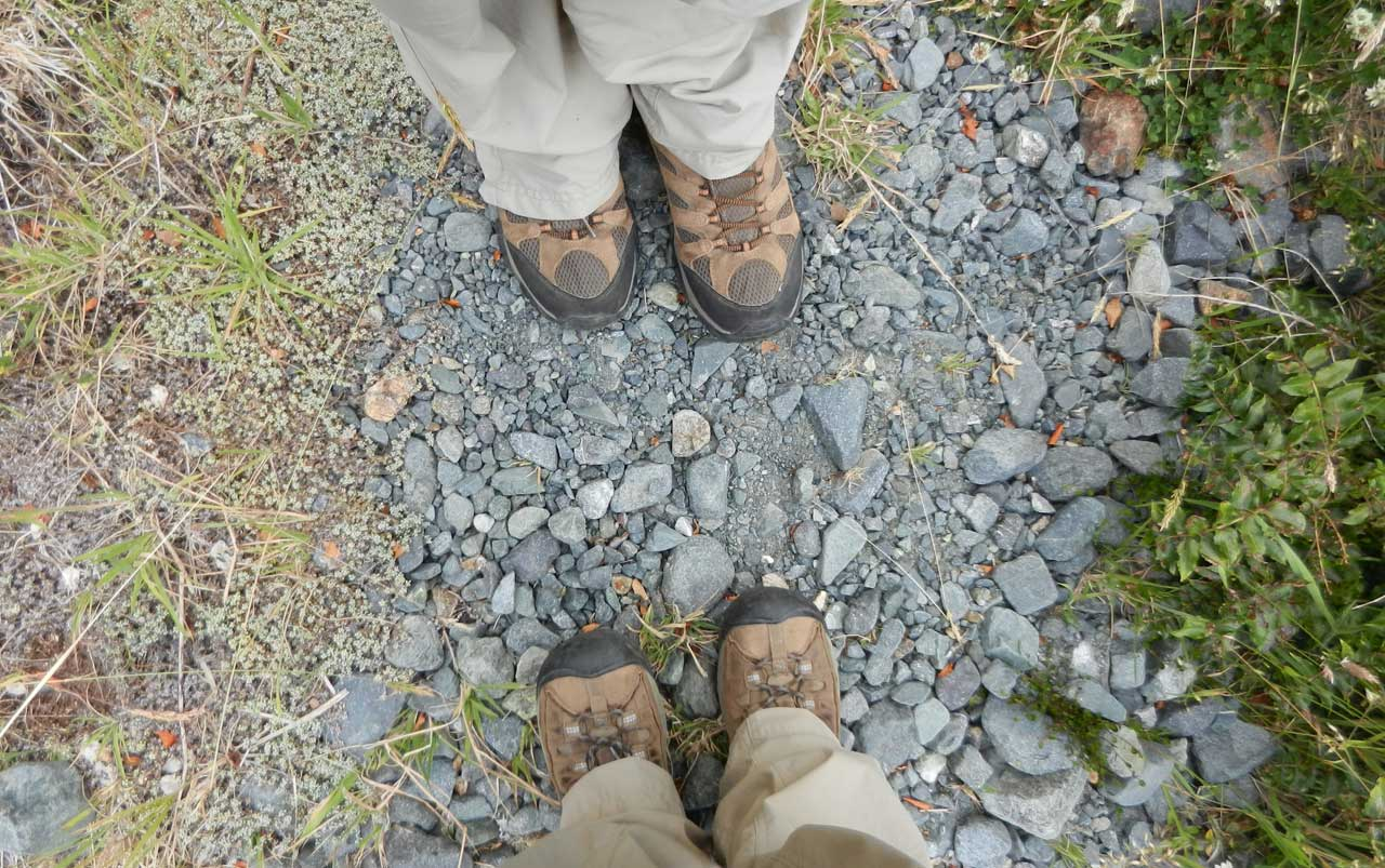 Woman's feet on the bottom, man's feet on the top - both wearing brown hiking boots - standing on blueish-grey rocks.