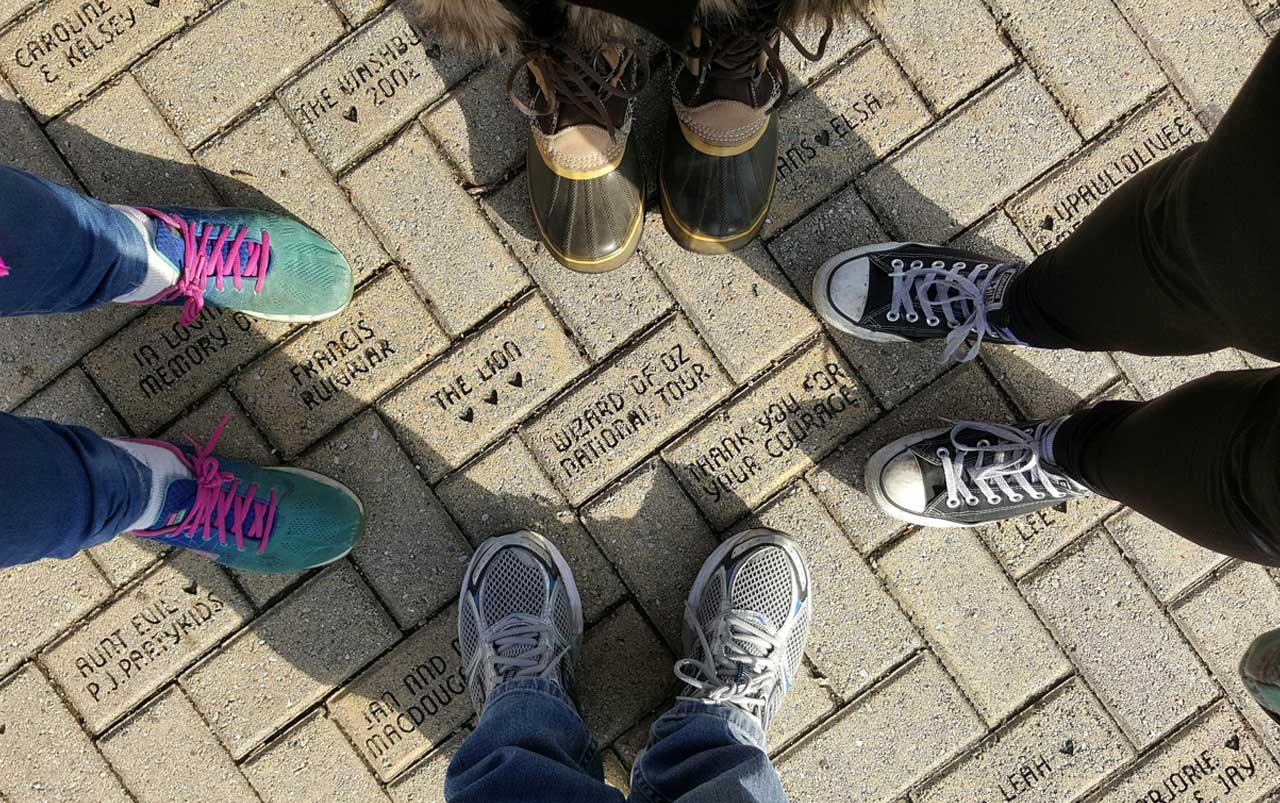 Four sets of feet standing on a yellow-colored brick walkway.