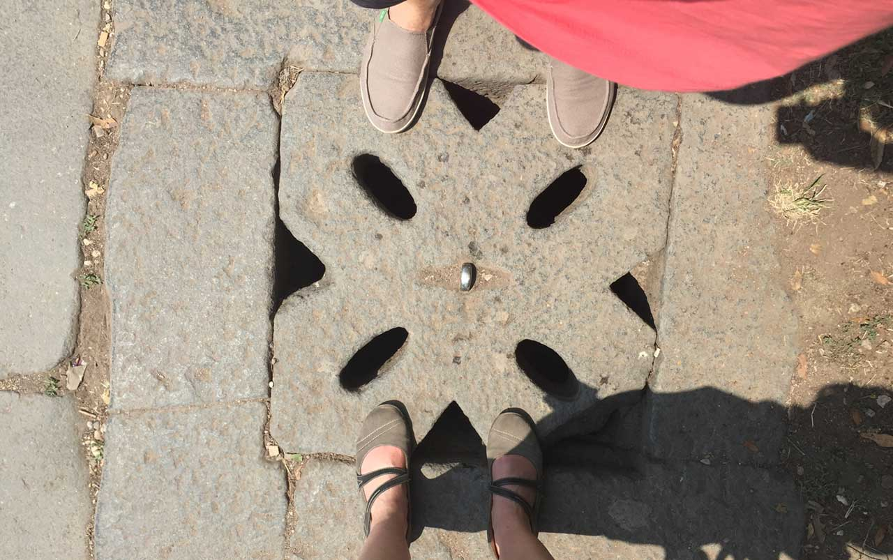 Woman's feet wearing grey shoes at the bottom, man's feet wearing tan shoes at the top, standing near a patterned square block in the sidewalk.