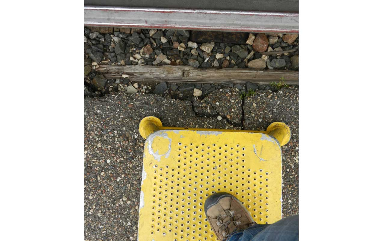 Single woman's foot wearing a brown hiking boot stepping on a square yellow stool.
