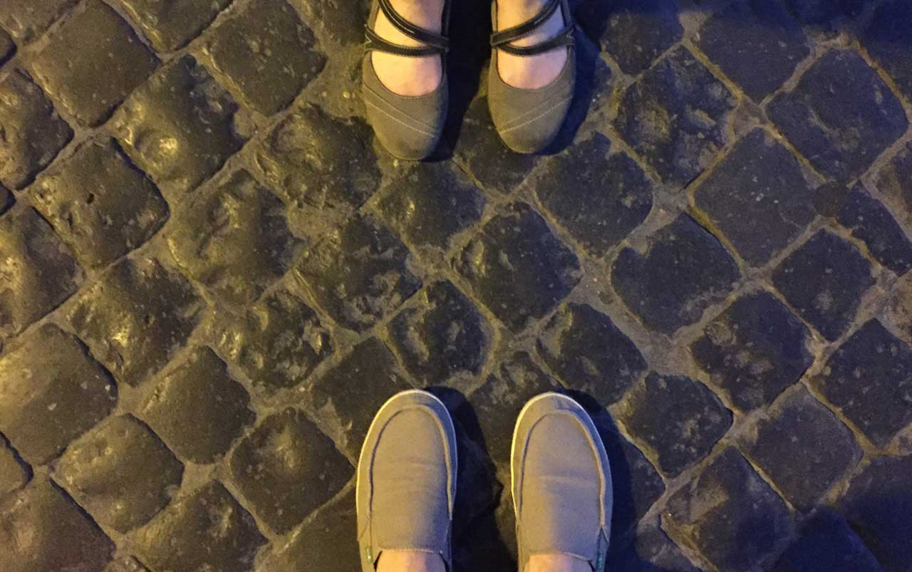 Man's feet wearing tan shoes at the bottom, woman's feet wearing grey shoes at the top standing on a walkway made up of black square pavers.