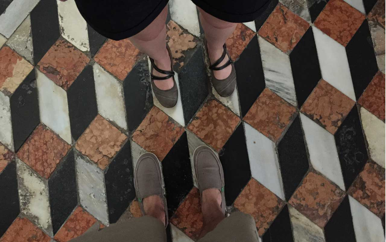 Man's feet at the bottom and woman's feet at the top of the photo standing on a black, white, and red-orange geometrically patterned floor.