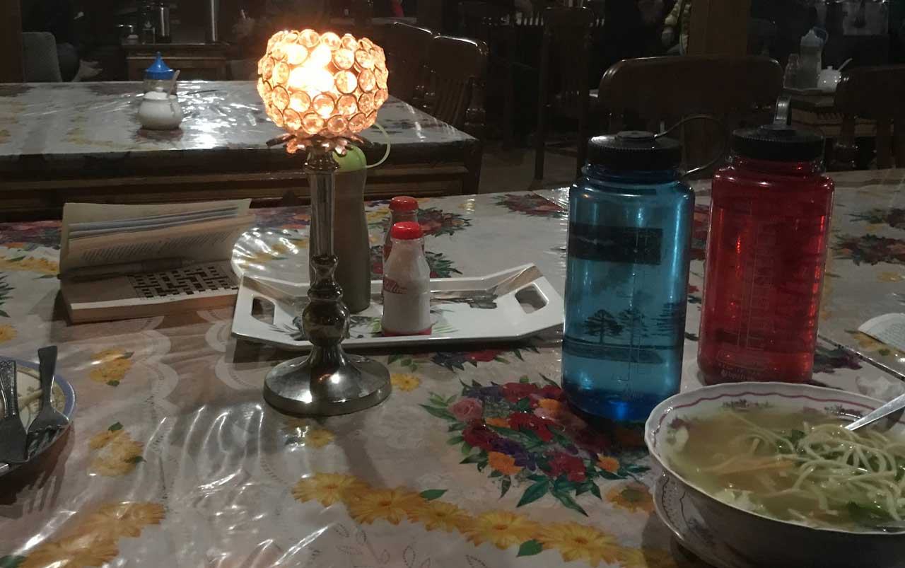 Tall candleholder holding a lit candle, with a bowl of soup and two large water bottles placed next to it.