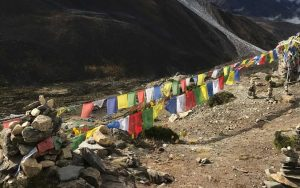 Prayer flags spread across an area surrounded by stacked rock cairns.
