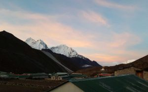 Snow capped mountain peaks surrounding a village in the valley against a blue sky with pink clouds at sunrise.