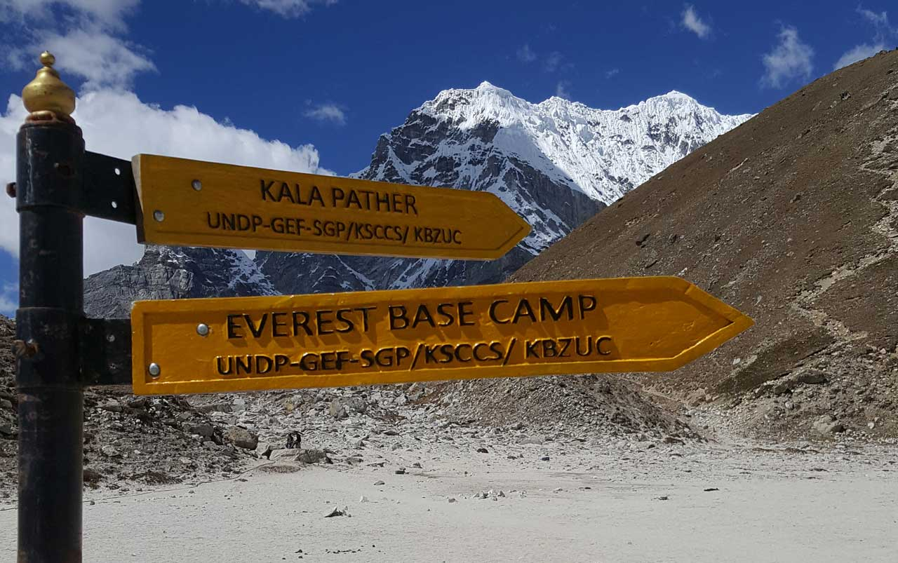 Yellow arrow signs pointing the direction to Kala Patthar and Everest Base Camp with mountains in the background.