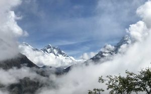 Mountain peaks surrounded by white clouds against a blue sky.