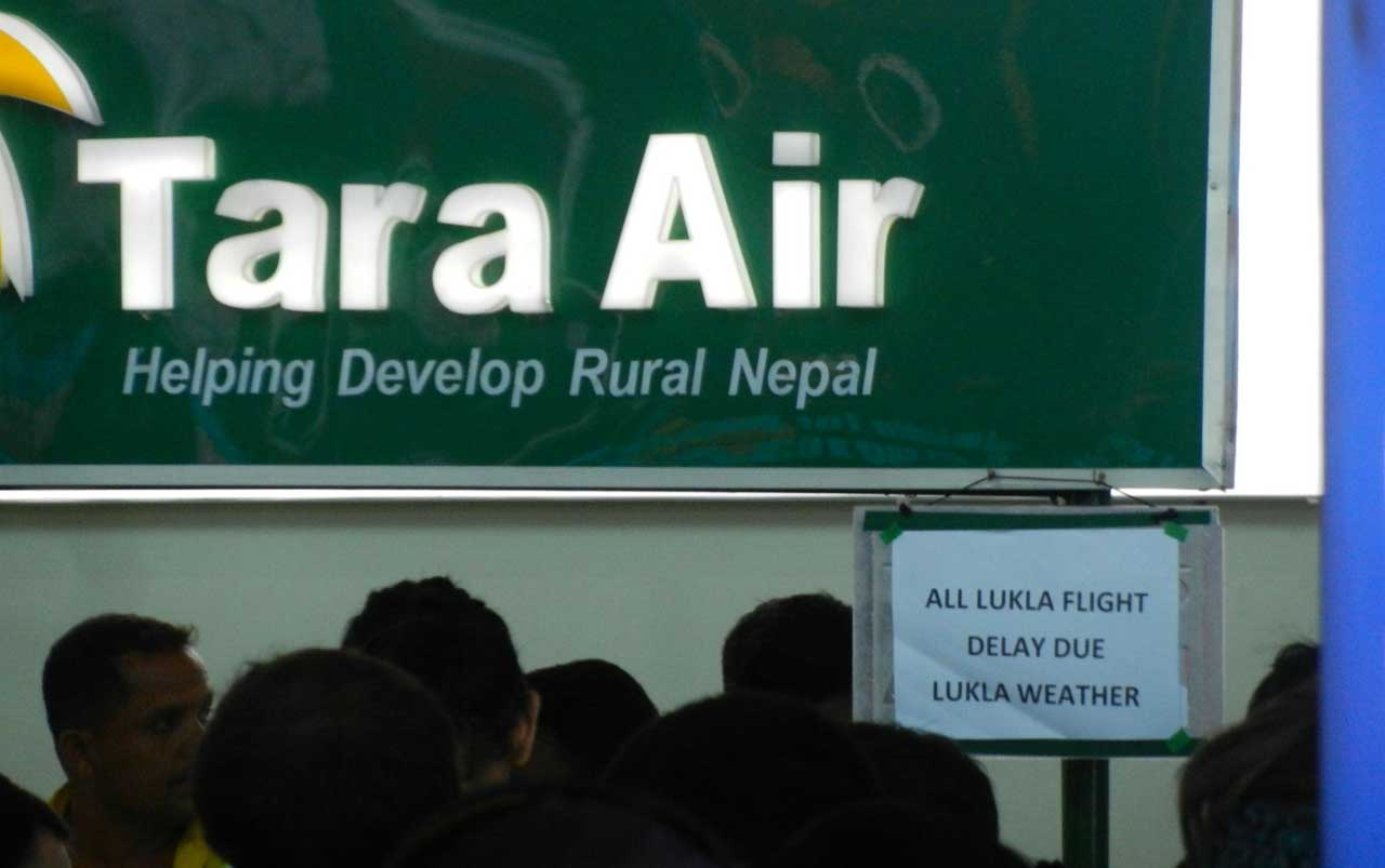 """Crowd of people standing in front of an airline kiosk with a green sign with Tara Air in white and a clipboard holding a white piece of paper with black letters reading """"All Lukla flight delay due Lukla weather""""."""