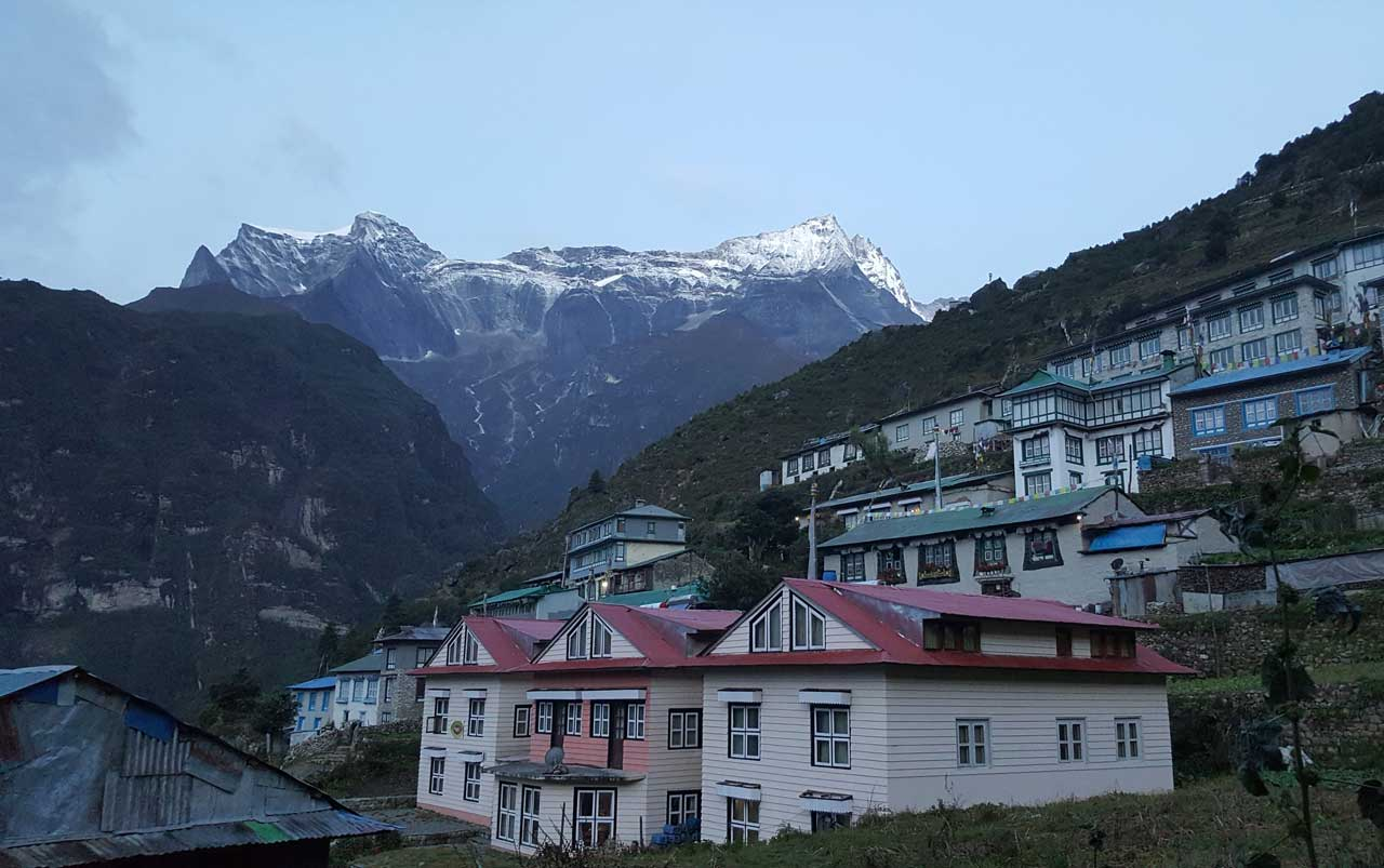 Mountain peaks in the distance, with village buildings in the foreground.