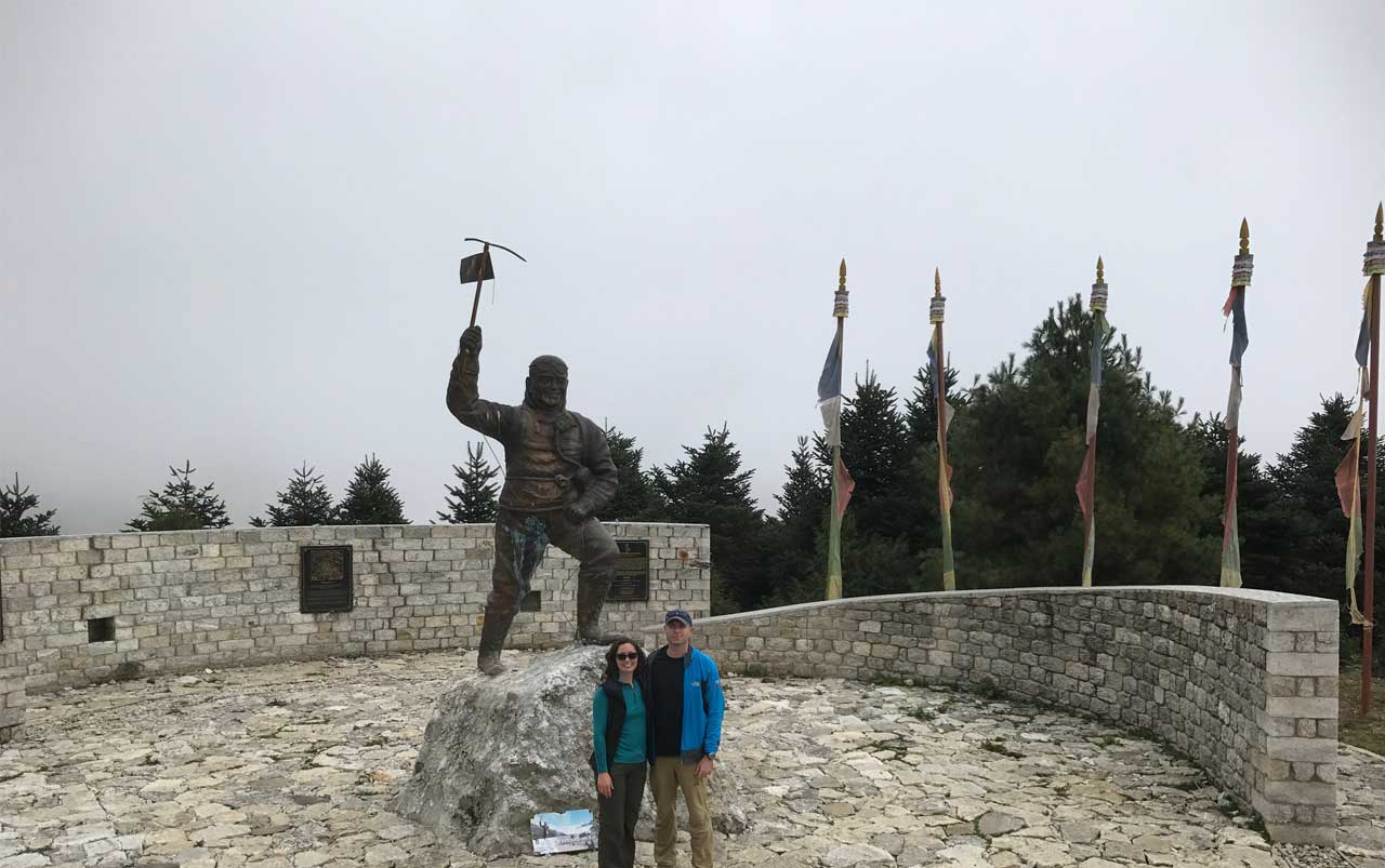 Young couple standing in front of a bronze statue of a man holding a pickax in front of cloudy skies.