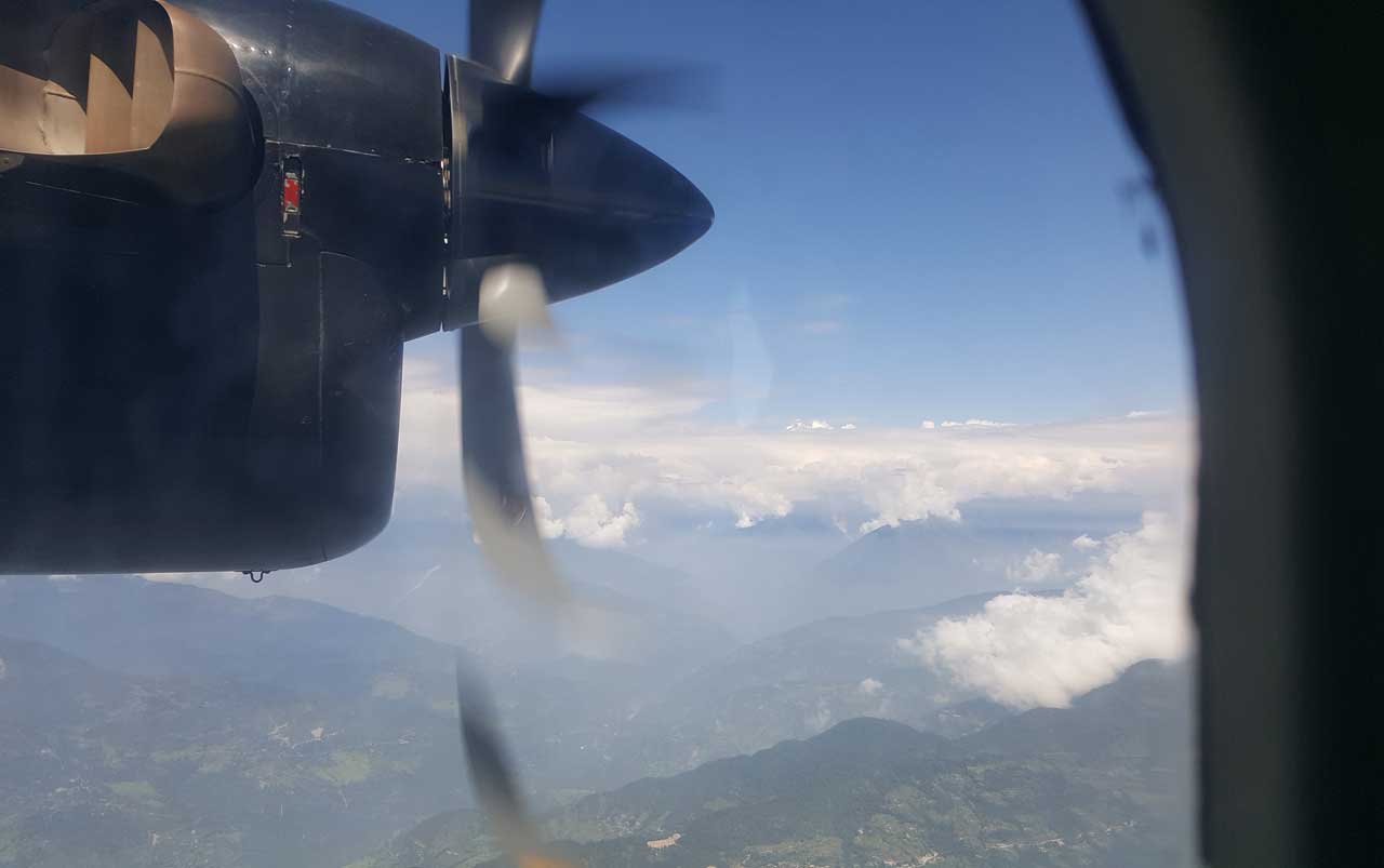 View of airplane propeller engine with mountainous valleys below.
